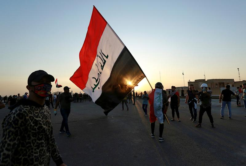 People walk through Khilani Square after protesters took control and reopened it after clashes between Iraqi security forces and anti-government demonstrators in Baghdad, Iraq, Saturday, Nov. 16, 2019. (AP Photo/Hadi Mizban)