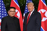 Standing in front of the flags of their two countries, Donald Trump and Kim Jong Un made history in Singapore
