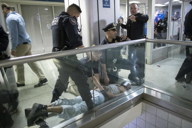 New York City police officers detain a passenger from a disabled New Jersey Transit train who became belligerent and sparked a stampede among passengers leaving the overcrowded station once the train finally arrived at New York's Penn Station, Friday, April 14, 2017. The New Jersey Transit train with about 1,200 passengers aboard was stuck in a Hudson River tunnel between New York and New Jersey for nearly three hours. (AP Photo/Mary Altaffer)