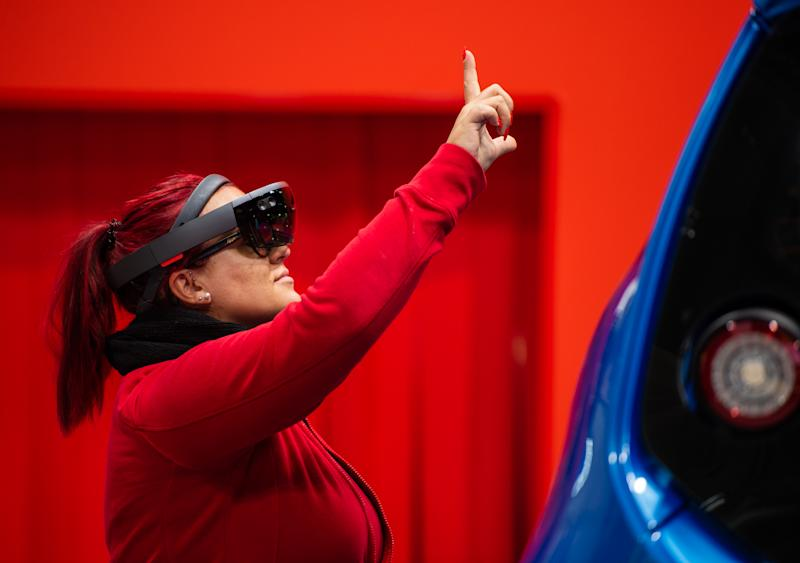 31 March 2019, Lower Saxony, Hannover: At a stand of the German manufacturer of drive technology SEW Eurodrive, a woman stands on an automated production line with holographic glasses on which she receives work instructions and can check off with gestures. From 1 to 5 April, everything at Hannover Messe will revolve around networking, learning machines and the Internet of Things. Photo: Christophe Gateau/dpa (Photo by Christophe Gateau/picture alliance via Getty Images)