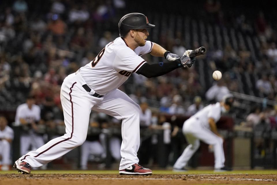 Arizona Diamondbacks' Merrill Kelly drops down a sacrifice bunt against the Miami Marlins during the fifth inning of a baseball game Thursday, May 13, 2021, in Phoenix. (AP Photo/Ross D. Franklin)