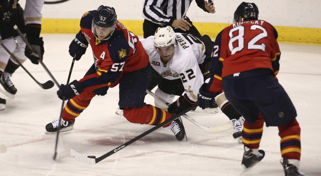Anaheim Ducks' Mathieu Perreault (22) works between Florida Panthers' Marcel Goc (57) and Tomas Kopecky (82) for the puck during the third period of an NHL hockey game in Sunrise, Fla., Tuesday, Nov. 12, 2013. The Panthers won 3-2. (AP Photo/J Pat Carter)