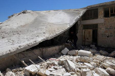 Men salvage a motorbike amid the damage from inside a medical point at a site hit by airstrikes on Tuesday, in the town of Khan Sheikhoun in rebel-held Idlib, Syria April 5, 2017. REUTERS/Ammar Abdullah