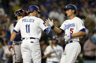 Los Angeles Dodgers' Corey Seager, right, is met at home plate by AJ Pollock after hitting a two-run home run during the third inning of a baseball game against the Atlanta Braves, Monday, Aug. 30, 2021, in Los Angeles. (AP Photo/Marcio Jose Sanchez)