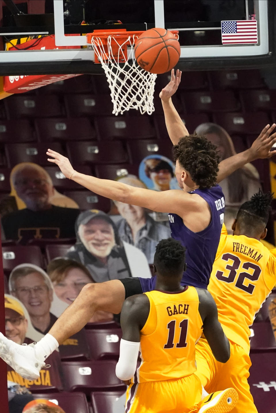 Northwestern's Ty Berry, center, lays up a shot between Minnesota's Both Gach (11) and Sam Freeman (32) in the first half of an NCAA college basketball game, Thursday, Feb. 25, 2021, in Minneapolis. (AP Photo/Jim Mone)