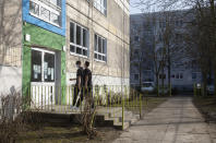 High school students Robin Reyer, left, and Mohammad Alshebli, 16 and 17 years old, enter the Arche, or Ark, an organization that supports children, youth and families, in the Hellersdorf neighbourhood, on the eastern outskirts of Berlin, Germany, Tuesday, Feb. 23, 2021. Since the outbreak of the coronavirus pandemic, the Arche has had to reduce their real face-to-face assistance or traditional classroom schooling as an offer for children, mainly from underprivileged families, drastically. Some kids are still allowed to come over in person, but only once every two weeks. (AP Photo/Markus Schreiber)