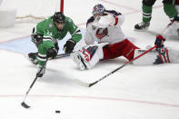 Dallas Stars center Andrew Cogliano (11) lunges for the puck after it was deflected by Columbus Blue Jackets goaltender Elvis Merzlikins (90) in the second period during an NHL hockey game on Thursday, April 15, 2021, in Dallas. (AP Photo/Richard W. Rodriguez)