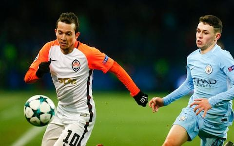 Bernard playing for Shakhtar challenges for the ball with Manchester City's Phil Foden - Credit: AP