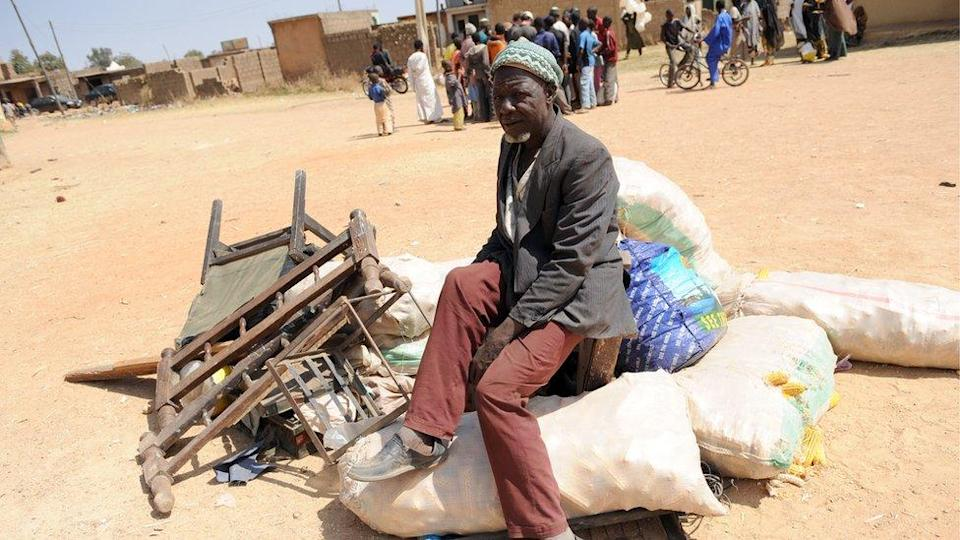A displaced man sits on his household in Jos, Plateau State