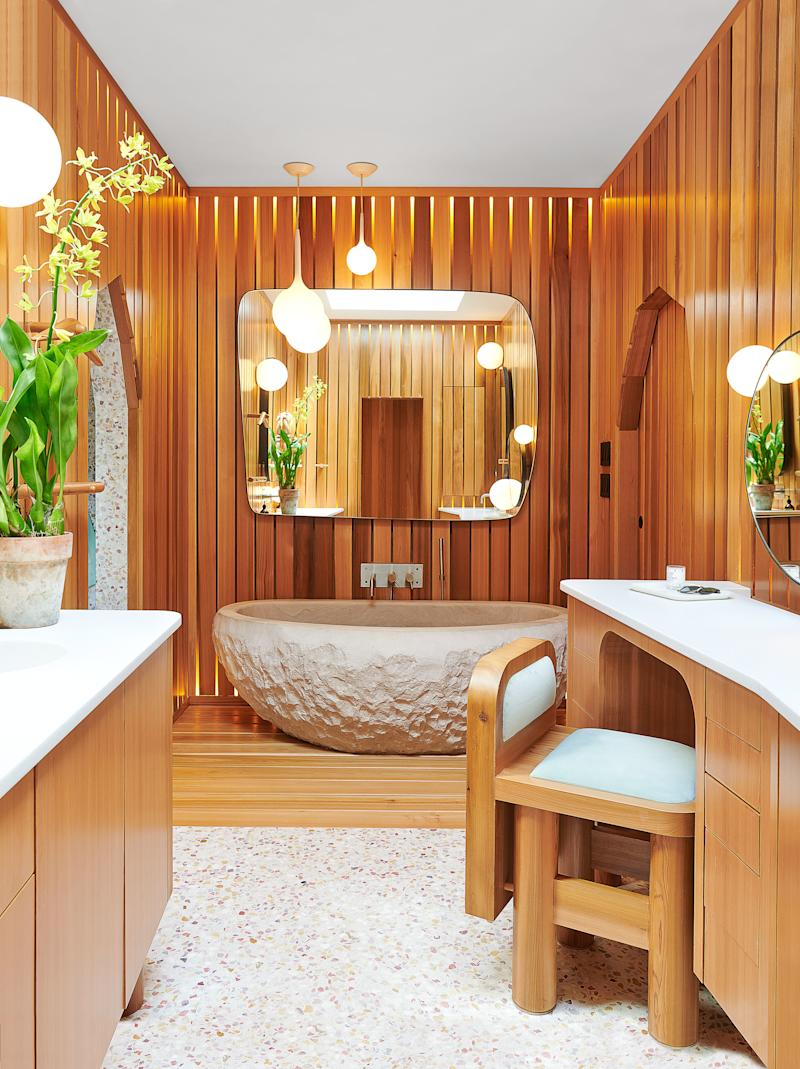 A backlit cedar screen by Snarkitecture illuminates the master bath. Custom tub, mirror, cedar vanity, and chair by Snarkitecture.