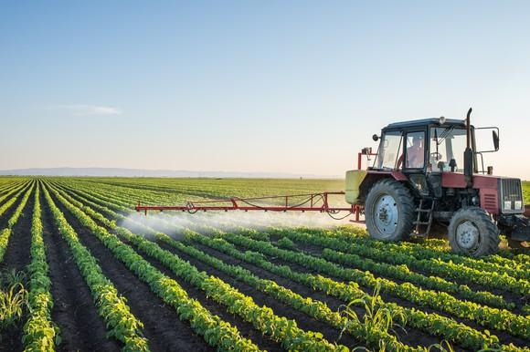 A tractor spraying nutrients on planted crops.