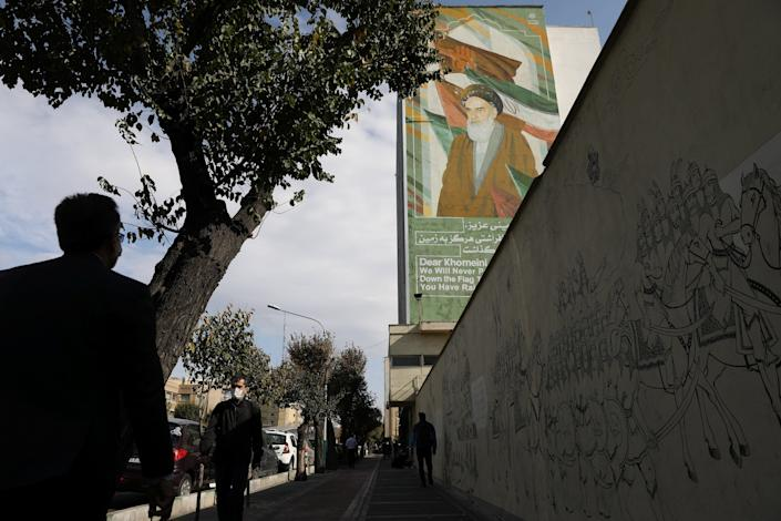 People walk on a pavement as a banner depicting Iran's late leader Ayatollah Ruhollah Khomeini. Majid Asgaripour/WANA (West Asia News Agency) via REUTERS ATTENTION EDITORSVia REUTERS