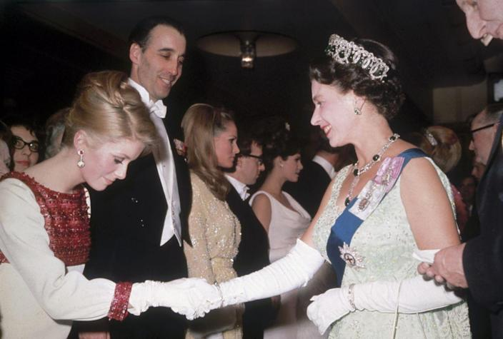 <p>French actress Catherine Deneuve greeted Queen Elizabeth with a respectful curtsy, which is all fine and good, but can we talk about her dress?! The red beading details. The matching earrings. It's all so good. <br></p>