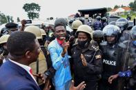Ugandan presidential candidate Robert Kyagulanyi is led into a vehicle by riot policemen in Luuka district