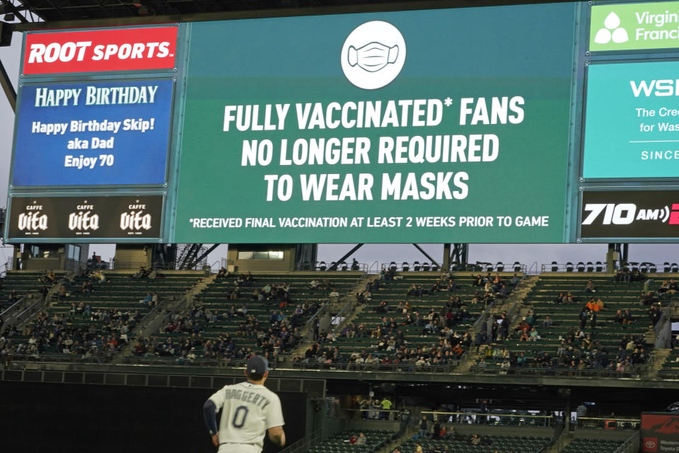 Fans sit in a special section for people who are fully vaccinated against COVID-19, at T-Mobile Park during a baseball game between the Seattle Mariners and the Detroit Tigers, Monday, May 17, 2021, in Seattle. Monday was the first day that fans fully vaccinated against COVID-19 were not required to wear masks at the ballpark, as shown on the video display. (AP Photo/Ted S. Warren)
