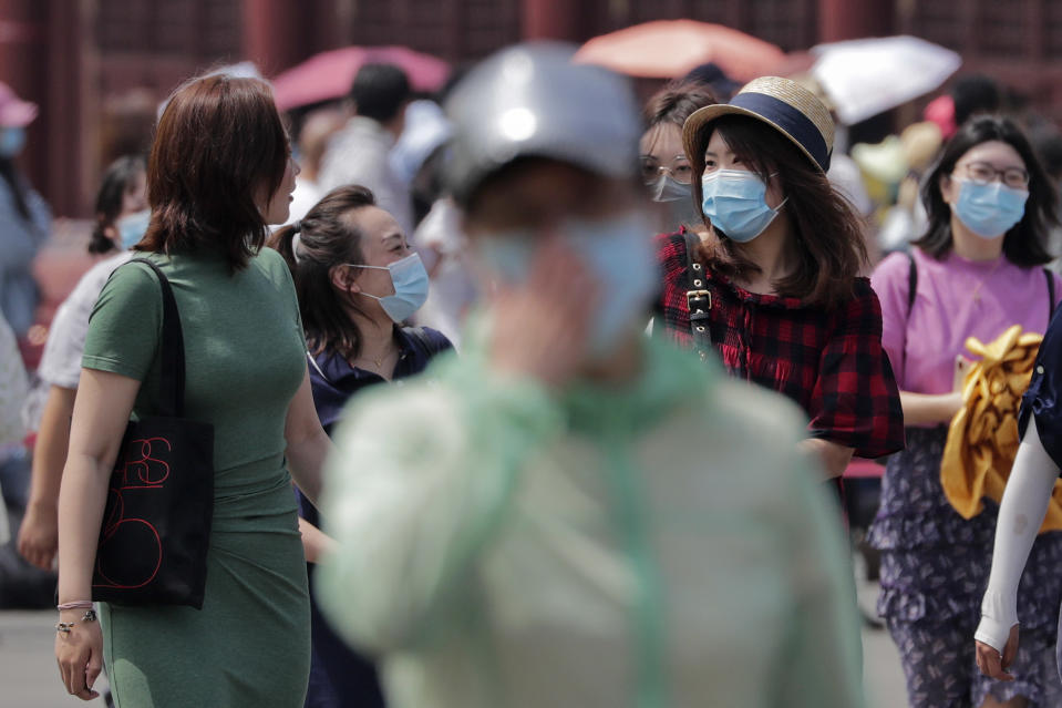 Women wearing face masks to protect against the spread of the new coronavirus share a light moment as they visit Forbidden City in Beijing, Thursday, May 28, 2020. South Korea on Thursday reported its biggest jump in coronavirus cases in more than 50 days, a resurgence that health officials warn is getting harder to track and risks erasing some of the nation's hard-won gains. (AP Photo/Andy Wong)