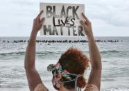 FILE - In this June 5, 2020, file photo, Shawna Ventimiglia from Manhattan Beach holds a sign in support of a local group of surfers during a traditional paddle out ceremony in Hermosa Beach in support of Black Lives Matter over the death of George Floyd in Los Angeles. The Black Lives Matter Global Network Foundation, which grew out of the creation of the Black Lives Matter movement, is formally expanding a $3 million financial relief fund that it quietly launched in February 2021, to help people struggling to make ends meet during the ongoing coronavirus pandemic. (AP Photo/Richard Vogel, File)