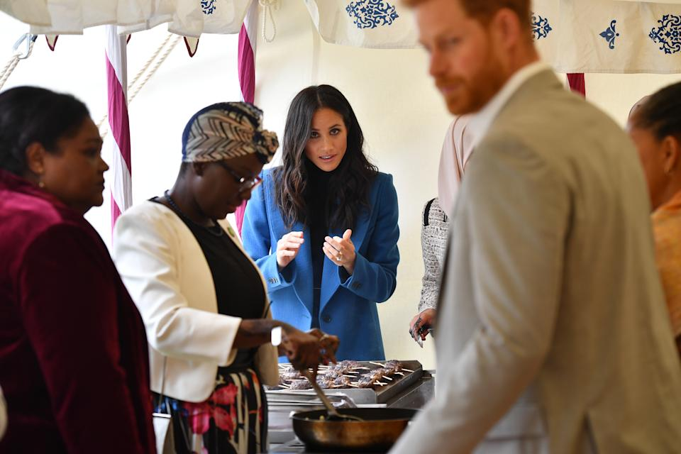 LONDON, ENGLAND - SEPTEMBER 20: Meghan, Duchess of Sussex (3L) helps to prepare food at an event to mark the launch of a cookbook with recipes from a group of women affected by the Grenfell Tower fire at Kensington Palace on September 20, 2018 in London, England. (Photo by Ben Stansall - WPA Pool/Getty Images)