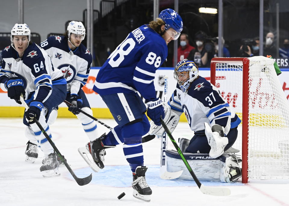 Toronto Maple Leafs right wing William Nylander (88) tries to screen Winnipeg Jets goaltender Connor Hellebuyck (37) during third-period NHL hockey game action in Toronto, Ontario, Monday, Jan. 18, 2021. (Nathan Denette/The Canadian Press via AP