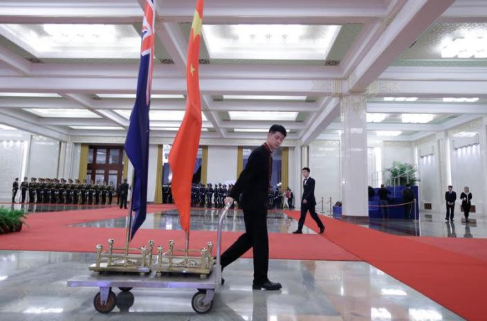 An attendant moves flags of New Zealand and China after a welcome ceremony in Beijing