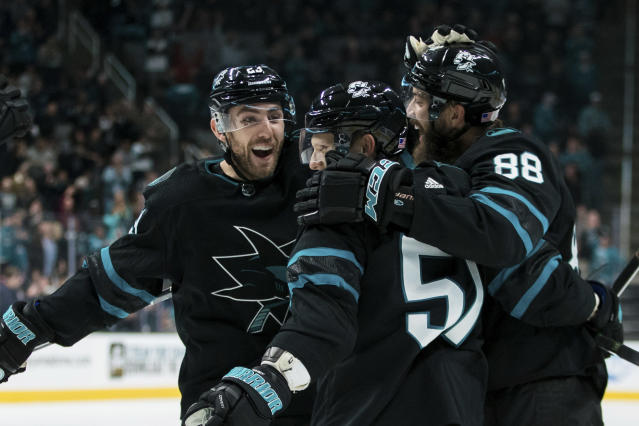 San Jose Sharks' Radim Simek, middle, is congratulated by Brent Burns (88) and right wing Barclay Goodrow, left, after scoring a goal against the Minnesota Wild during the first period of an NHL hockey game Thursday, Nov. 7, 2019, in San Jose, Calif. (AP Photo/John Hefti)