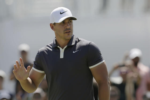 Brooks Koepka acknowledges applause after putting on the first hole of the final round in the Northern Trust golf tournament at Liberty National Golf Course, Sunday, Aug. 11, 2019 in Jersey City, N.J. (AP Photo/Mark Lennihan)
