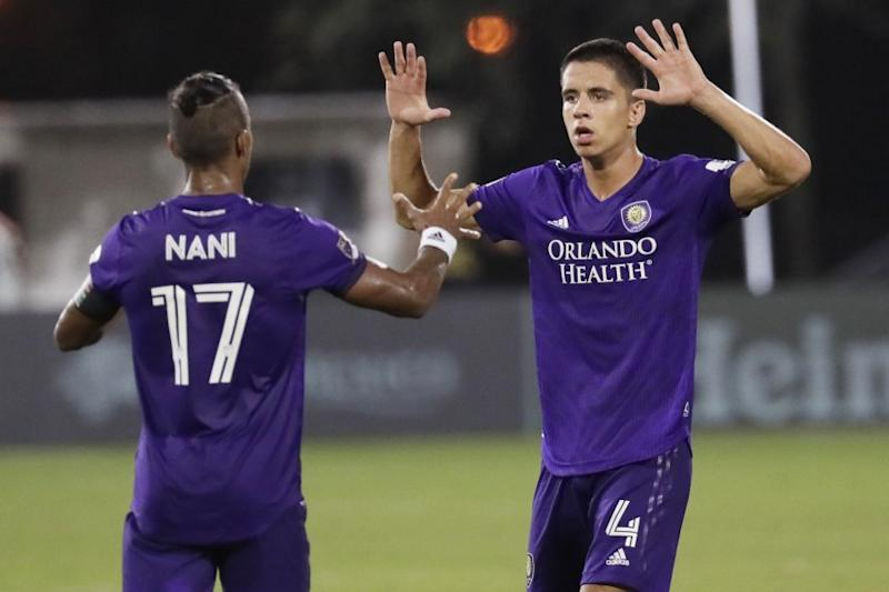 Orlando City defender Joao Moutinho (4) celebrates a goal with teammate Orlando City forward Nani (17) during the second half of an MLS soccer match, Friday, July 31, 2020, in Orlando, Fla. (AP Photo/John Raoux)