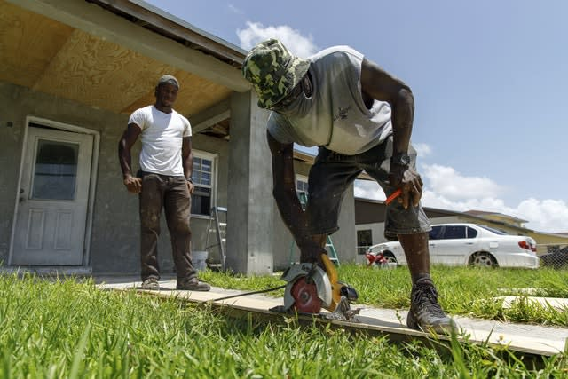 Darrel Duncombe stands nearby as Max Hall cuts a sheet of plywood to use to repair a roof in preparation for the arrival of Hurricane Isaias in Freeport, Grand Bahama, Bahamas (Tim Aylen/AP)