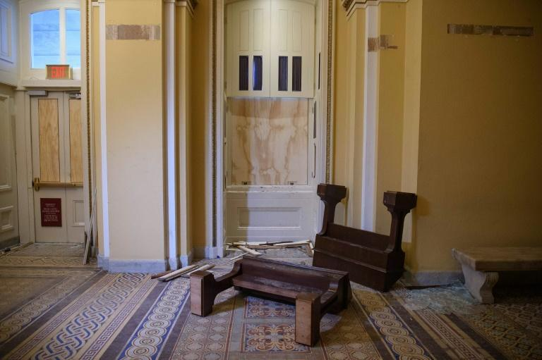Overturned furniture and broken glass litter a hallway of the US Capitol after the crowd invasion