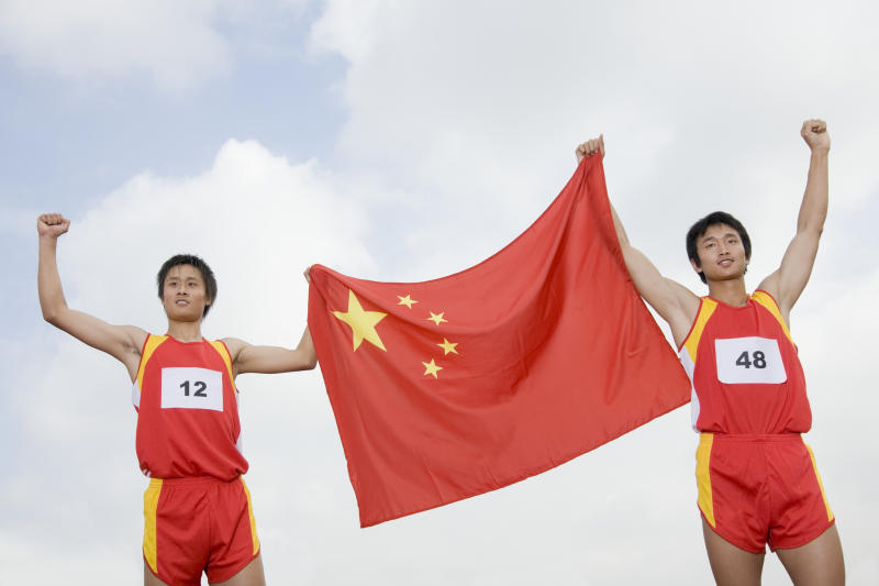Two Chinese athletes holding a Chinese flag between them.