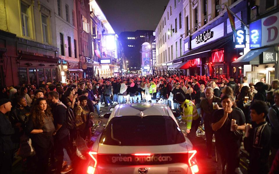 A car tries to drive through a crowded Soho street - Justin Tallis/AFP