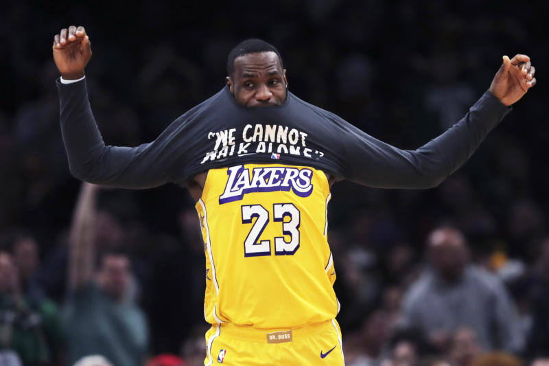 Los Angeles Lakers forward LeBron James puts on a warm-up shirt as he goes to the bench during the first half of an NBA basketball game against the Boston Celtics in Boston, Monday, Jan. 20, 2020. (AP Photo/Charles Krupa)