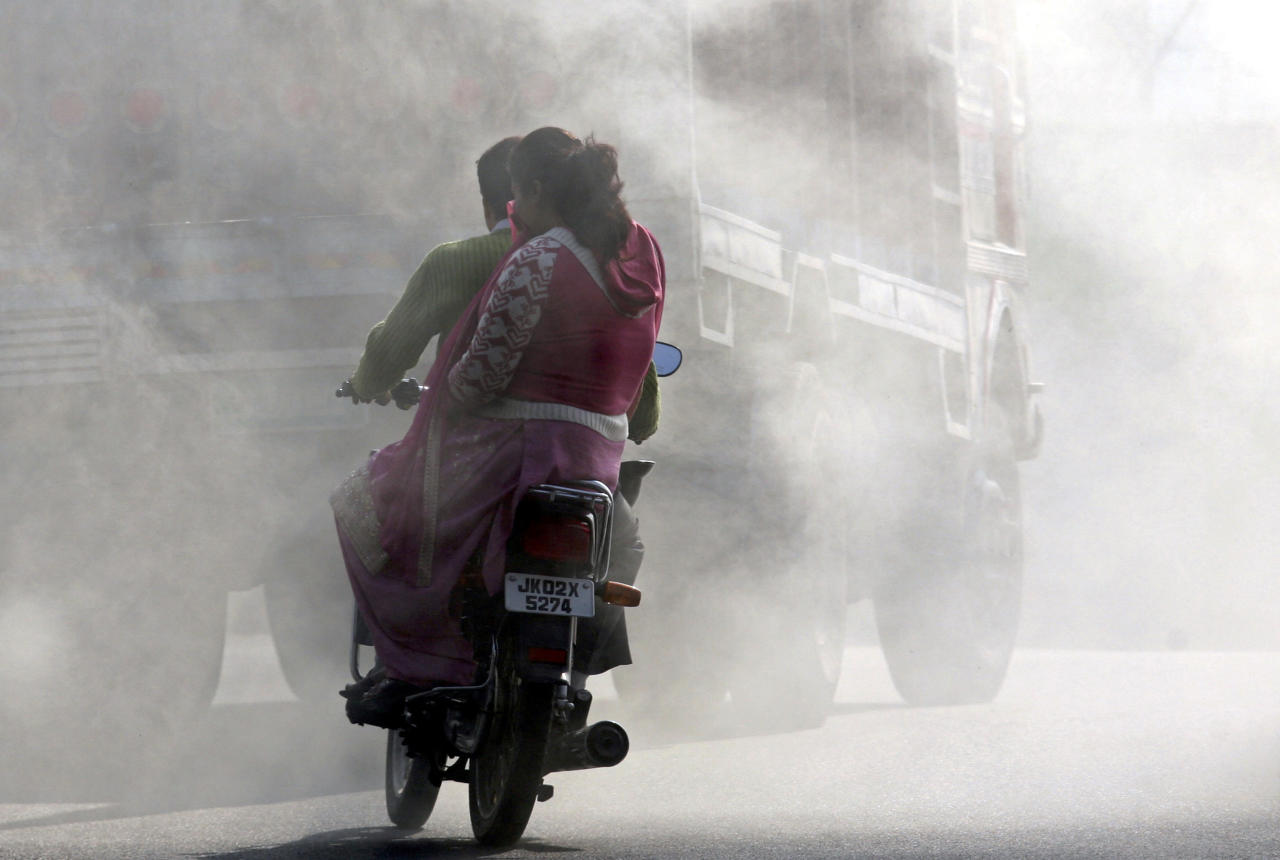 "A woman on a motorcycle covers her face from smoke coming from burning garbage dump in Jammu December 7, 2009. The biggest climate meeting in history, with 15,000 participants from 192 nations, opened in Copenhagen on Monday with hosts Denmark saying an unmissable opportunity to protect the planet was ""within reach"". REUTERS/Mukesh Gupta (INDIAN-ADMINISTERED KASHMIR ENVIRONMENT SOCIETY TRANSPORT)"
