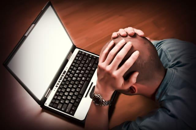 man lying down on bamboo floor has problem with his laptop