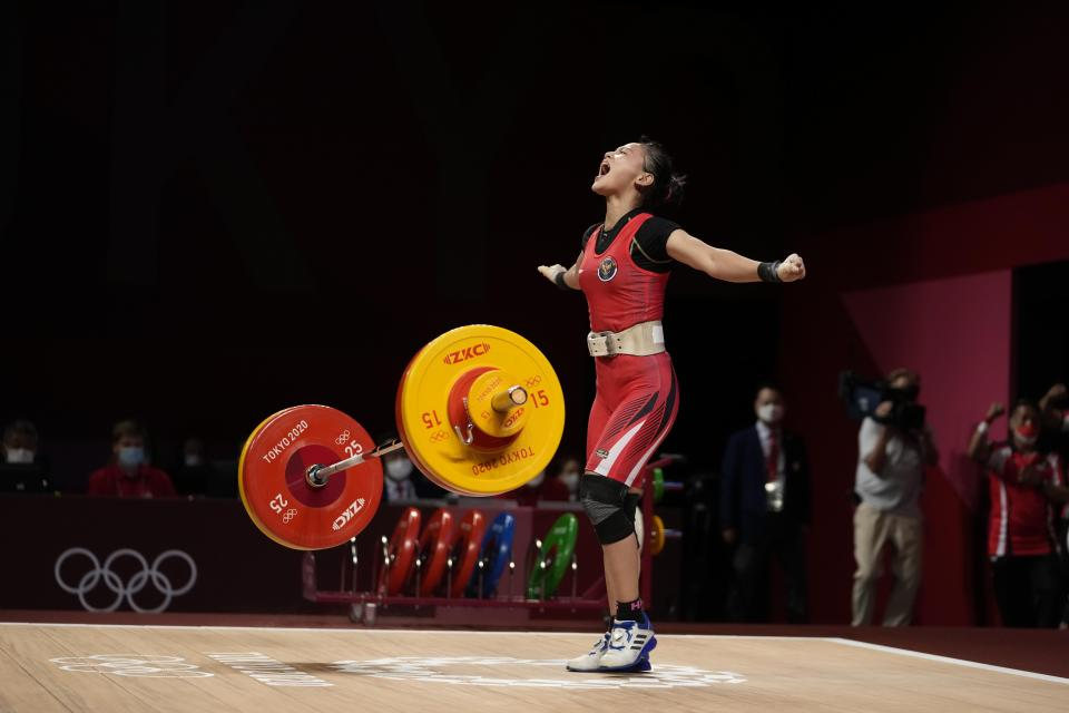 Windy Cantica Aisah of Indonesia celebrates after a lift as she competes in the women's 49kg weightlifting event, at the 2020 Summer Olympics, Saturday, July 24, 2021, in Tokyo, Japan. (AP Photo/Luca Bruno)