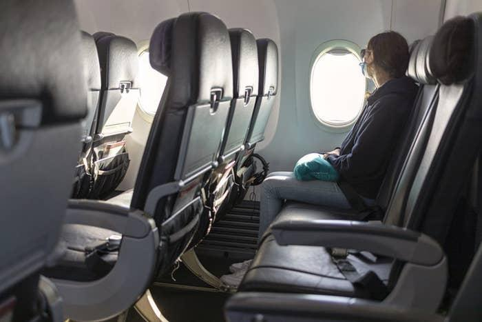 A woman looking out the window on a plane