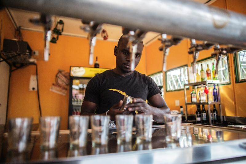A barman fills glasses with Soweto Gold craft beer at the Ubuntu Kraal Brewery on May 13, 2015 in Soweto, Johannesburg (AFP Photo/Gianluigi Guercia)