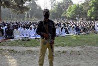 A police officer stands guard while Muslims perform an Eid al-Fitr prayer at a ground, in Quetta, Pakistan, Thursday, May 13, 2021. Millions of Muslims across the world are marking a muted and gloomy holiday of Eid al-Fitr, the end of the fasting month of Ramadan - a usually joyous three-day celebration that has been significantly toned down as coronavirus cases soar. (AP Photo/Arshad Butt)