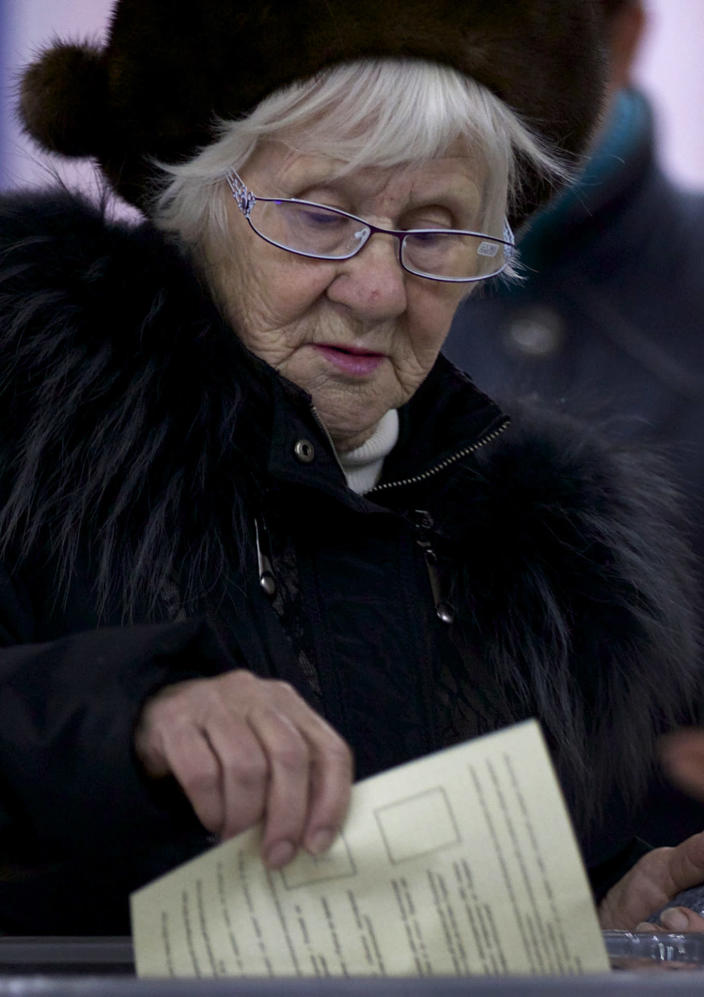 A woman casts her ballot at a polling station in Simferopol, Ukraine, Sunday, March 16, 2014. Residents of Ukraine's Crimea region are voting in a contentious referendum on whether to split off and seek annexation by Russia. (AP Photo/Ivan Sekretarev)
