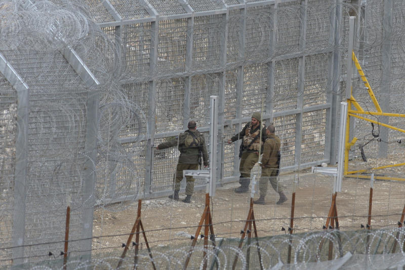 """Israeli soldiers stand on the border fence between Majdal Shams in the Golan Heights, and Syria, as security is tightened ahead of Land Day, Thursday, March 29, 2012. March 30 is traditionally marked by Israeli Arabs as """"Land Day,"""" a time of protests against the confiscation of Arab-owned lands by Israel. In recent years, Palestinians have joined in.(AP Photo/Hamad Almakt) ISRAEL OUT"""