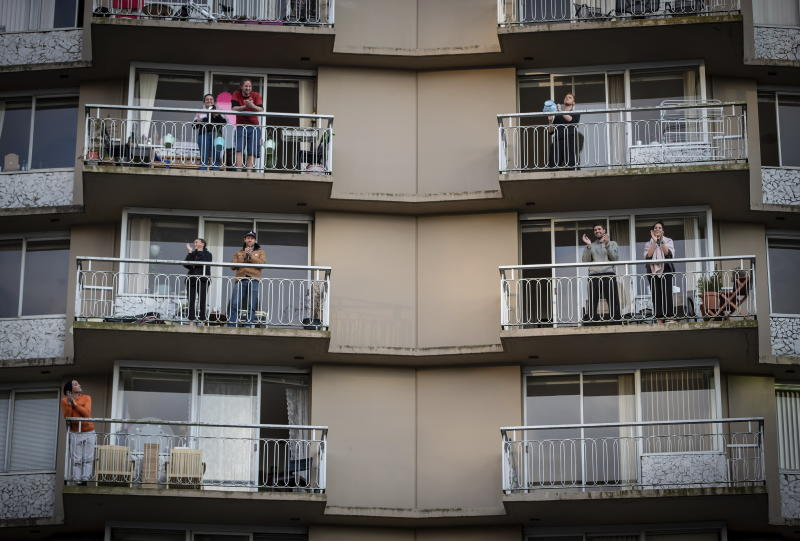 People on apartment balconies applaud and make noise in a daily show of support for healthcare workers who are fight the coronavirus, in the West End of Vancouver, British Columbia, Tuesday, March 24, 2020. (Darryl Dyck/The Canadian Press via AP)