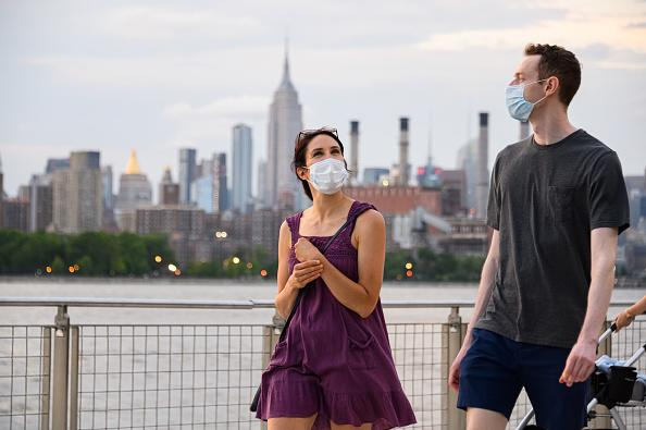 People wear protective face masks in Domino Park in Williamsburg, New York City.