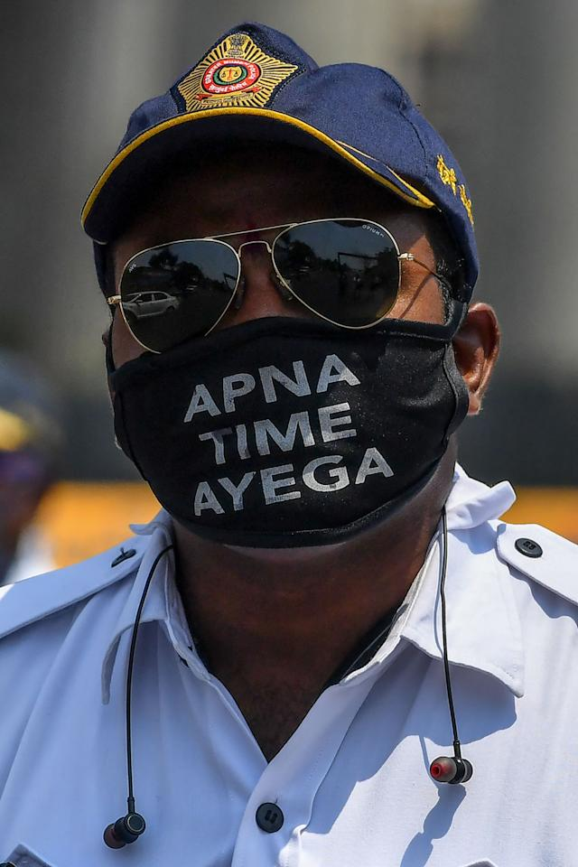 A policeman wears a facemask with a message from a popular Bollywood movie 'Gully Boy' saying in Hindi 'Our Time will come' at a checkpoint during a government-imposed nationwide lockdown as a preventive measure against the COVID-19 coronavirus, in Mumbai on March 31, 2020. (Photo by INDRANIL MUKHERJEE / AFP) (Photo by INDRANIL MUKHERJEE/AFP via Getty Images)