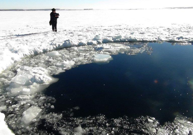 A police officer looks at a hole in a lake near Chebakul in Russia's Chelyabinsk region, on February 15, 2013