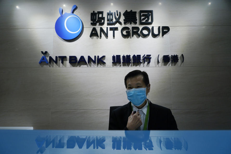 In this Friday, Oct. 23, 2020, photo, an employee sits at the Ant Group office in Hong Kong. The world's largest fintech company, China's Ant Group, will try to raise nearly $35 billion in a massive public offering of stock that would shatter records. (AP Photo/Kin Cheung)
