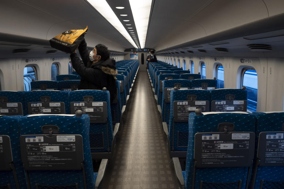 A traveler places his bag in an overhead luggage rack in a bullet train bound for Kyoto and Osaka at Tokyo Station in Tokyo, March 17, 2020. (AP Photo/Jae C. Hong)