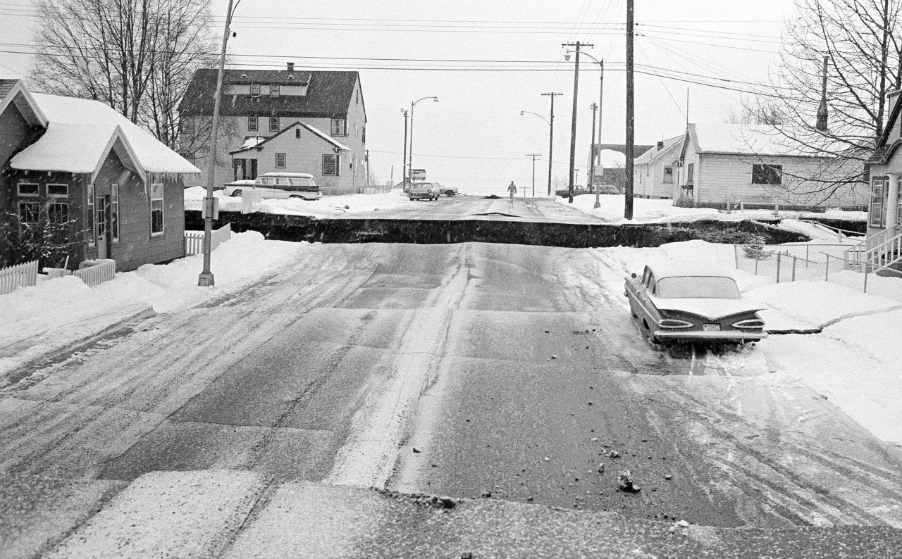 File - In this March 28, 1964 file photo, a huge crevasse is seen in the middle of a street in Anchorage, Alaska in the aftermath of an earthquake. One section of the street is several feet higher than the other. North America's largest earthquake rattled Alaska 50 years ago, killing 15 people and creating a tsunami that killed 124 more from Alaska to California. The magnitude 9.2 quake hit at 5:30 p.m. on Good Friday, turning soil beneath parts of Anchorage into jelly and collapsing buildings that were not engineered to withstand the force of colliding continental plates.(AP Photo/File)