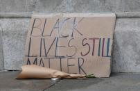 FILE PHOTO: A placard is pictured near the sculpture of a Black Lives Matter protester standing on the empty plinth previously occupied by the statue of slave trader Edward Colston, in Bristol