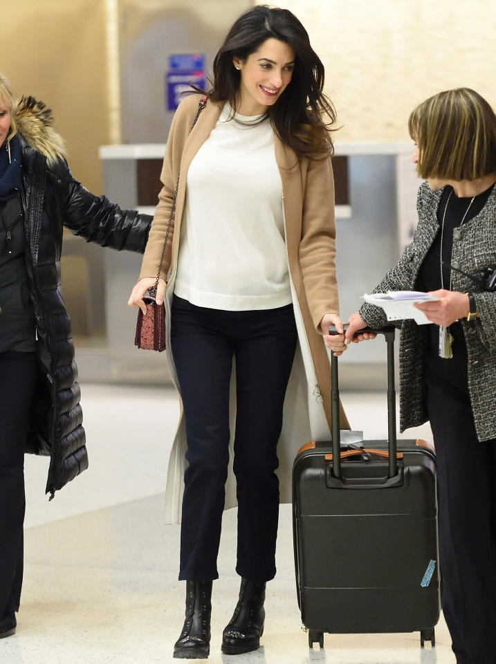 """<p>While at New York's JFK International Airport, Clooney sported a comfortable white sweater over black pants and black, laceless combat boots ($1,275; <a rel=""""nofollow"""" href=""""http://bit.ly/2ntlaaI"""">mytheresa.com</a>). She topped off the cozy travel outfit with a tan knee-length cardigan and a small crossbody bag.</p>"""