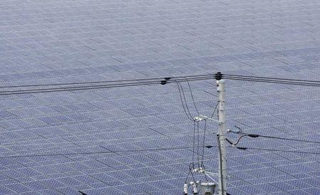 Power lines are seen in front of solar panels at a solar power field in Kawasaki